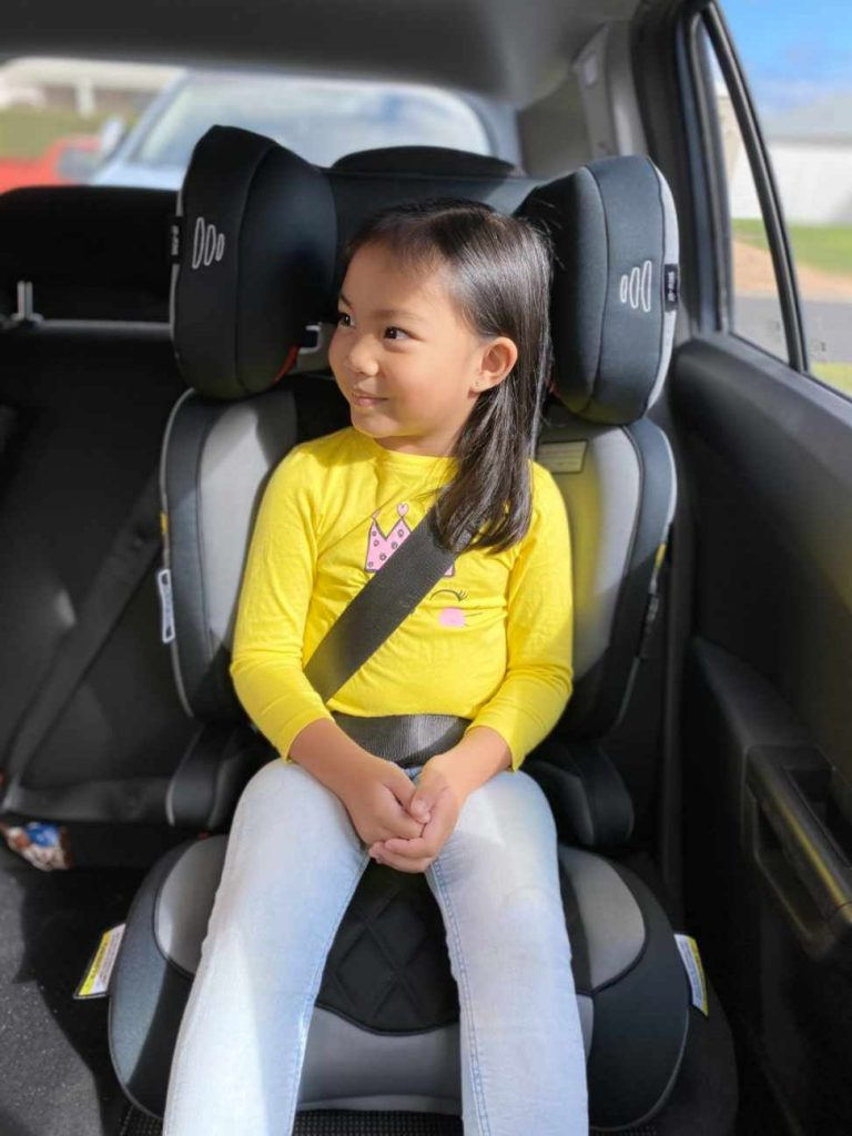Black and grey Infasecure booster seat with 4 year old child in lap sash booster
