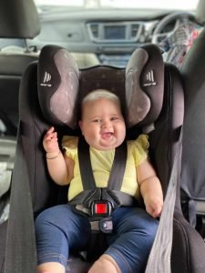 Smiling baby in a rear facing car seat wearing a yellow shirt and blue jeans