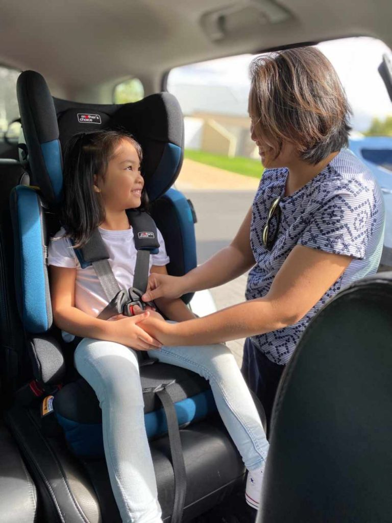 Mother buckling her child into a Mother's Choice convertible car booster seat. Car seat is installed on the passenger side.