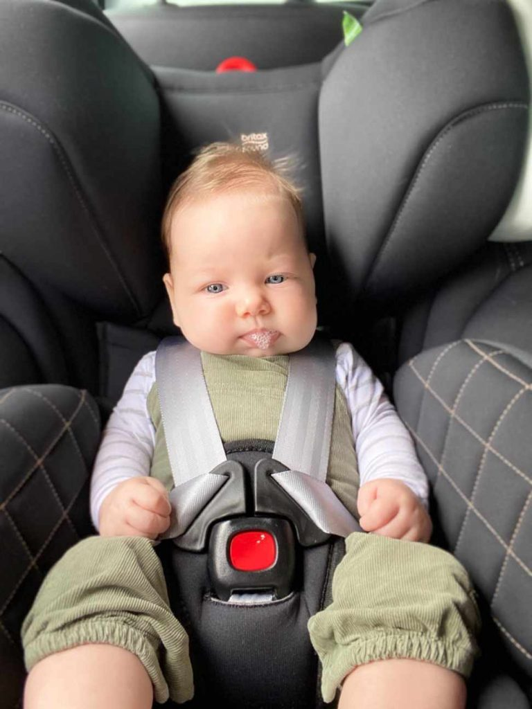 Grey Britax Millenia car seat with young baby blowing bubbles. Grey harness straps are firm and tight across baby's chest.