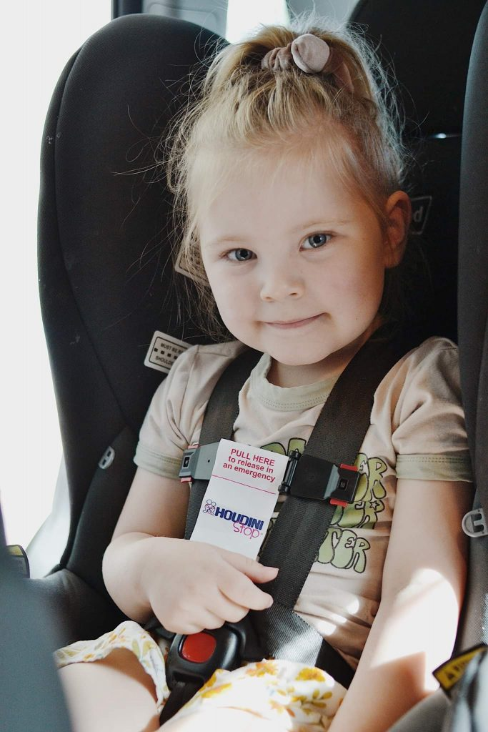 Child in black car seat with a Houdini strap across the harness to stop the child escaping their harness