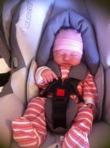 newborn Baby in capsule with pink stripey onesie